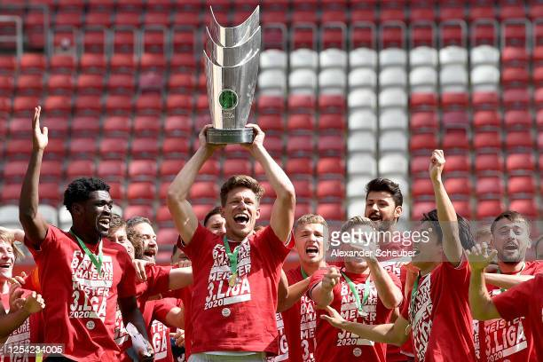 Team captain Nicolas Feldhahn of FC Bayern Muenchen II lifts the trophy to celebrate the championship following the 3. Liga match between 1. FC...
