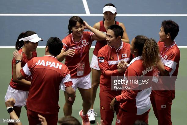 Team captain Toshihisa Tsuchihashi of Japan celebrates the 32 victory with members of the Japan Fed Cup team after the doubles match between Miyu...