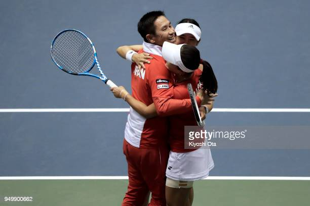 Team captain Toshihisa Tsuchihashi of Japan celebrates with Miyu Kato and Makoto Ninomiya of Japan after winning their doubles match against Johanna...