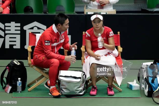 Team captain Toshihisa Tsuchihashi of Japan talks to Kurumi Nara of Japan in her singles match against Johanna Konta of Great Britain during day one...