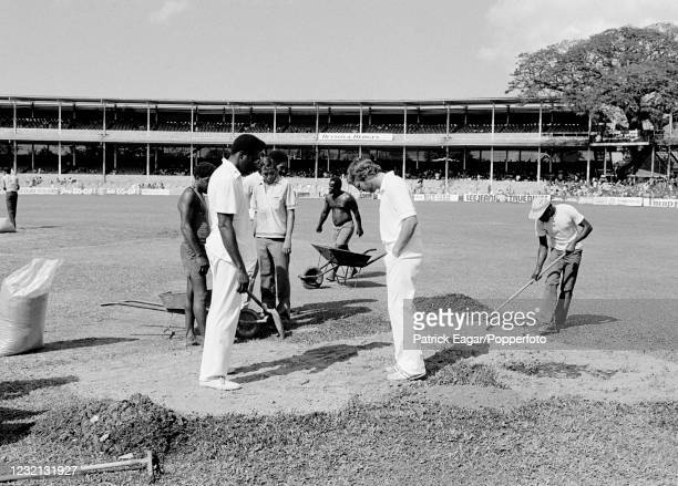 Team captains Clive Lloyd of West Indies and Ian Botham of England inspecting repair work being carried out on a patch of waterlogged outfield before...