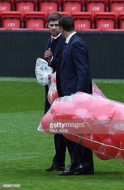 Team captains Liverpool's English midfielder Steven Gerrard and Everton's English defender Phil Jagielka prepare to release 96 balloons a memorial...