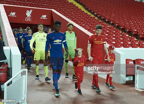 Team captains Matthew Virtue of Liverpool and Axel Tuanzebe of Manchester United lead their teams from the Anfield Tunnel during the Liverpool v...