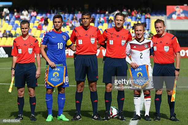 Team captains Nikola Moro of Croatia and Felix Passlack of Germany pose with the match officials prior to the FIFA U17 World Cup Chile 2015 Round of...