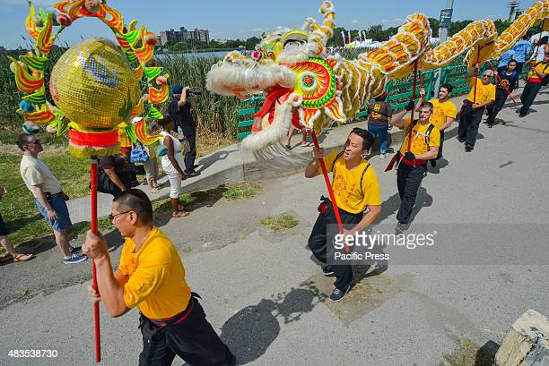 A team carries aloft a dragon puppet chasing the sun as they parade through the festival on the first day of the event The twoday 25th Annual Hong...