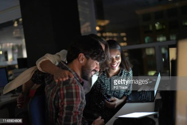 equipe que comemora e que abraça no escritório de noite - acabando - fotografias e filmes do acervo