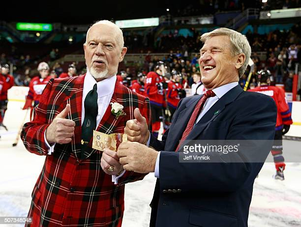 Team Cherry coach Don Cherry hands over a $100 bill to Team Orr coach Bobby Orr after losing a game winning bet at the CHL/NHL Top Prospects Game...