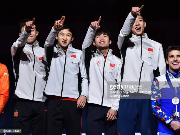 Team China react as they step onto the podium to receive their gold medals after finishing first in the men's 3000m relay final during the ISU World...