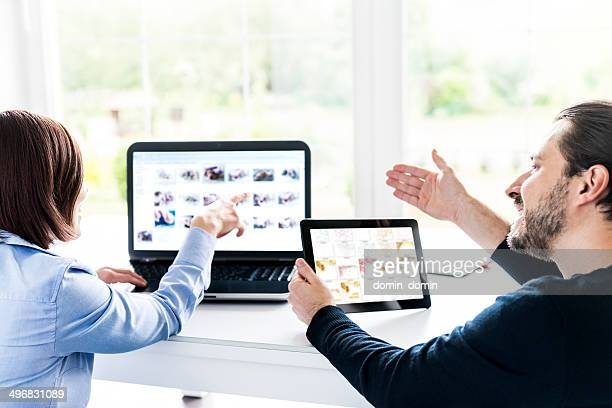 Team choosing images together on laptop and tablet, home office