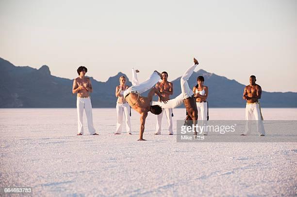 team clapping man performing capoeira on bonneville salt flats, utah, usa - capoeira imagens e fotografias de stock