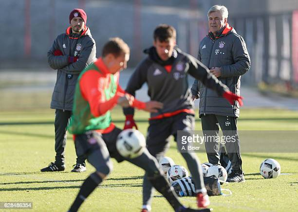 Team coach Carlo Ancelotti of FC Bayern Muenchen and assistent coach and son Davide Ancelotti watch the players practicing during a training session...