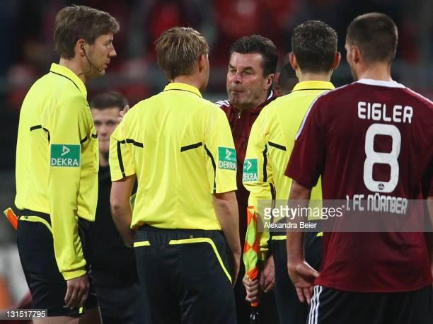 Team coach Dieter Hecking of Nuernberg speaks to referee Christian Dingert after the Bundesliga match between 1. FC Nuernberg and SC Freiburg at Easy...