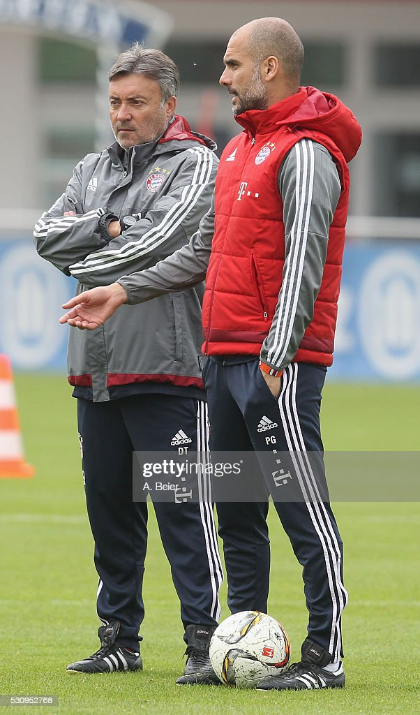 Team coach Josep Guardiola (R) and assistent coach Domenec Torrent of Bayern Muenchen chat during a training session at FC Bayern Muenchen training ground on May 12, 2016 in Munich, Germany.