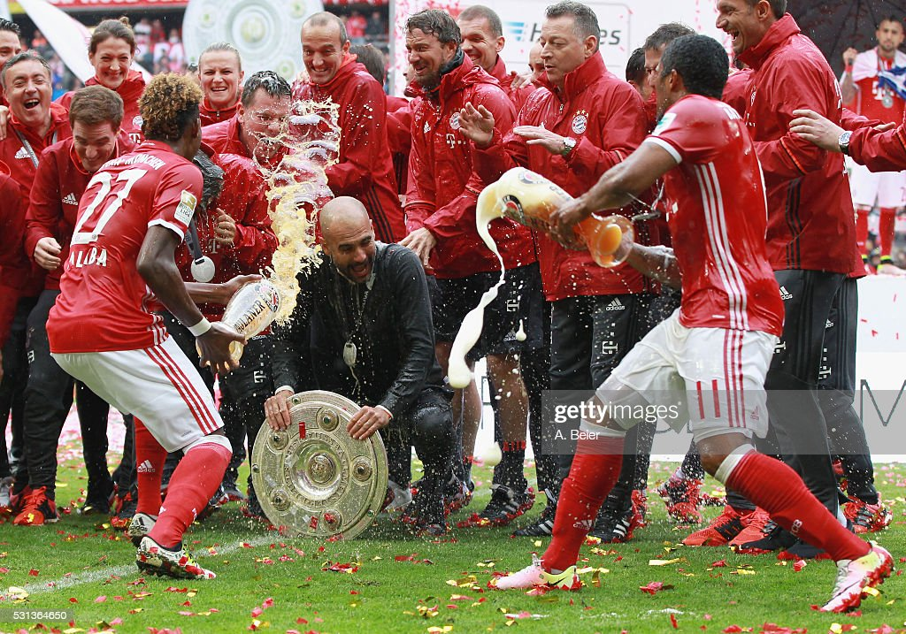 Team coach Josep Guardiola (C) of Bayern Muenchen receives a beer shower from David Alaba (L) and Douglas Costa during the German Championship celebration after the Bundesliga match between FC Bayern Muenchen and Hannover 96 at Allianz Arena on May 14, 2016 in Munich, Germany.
