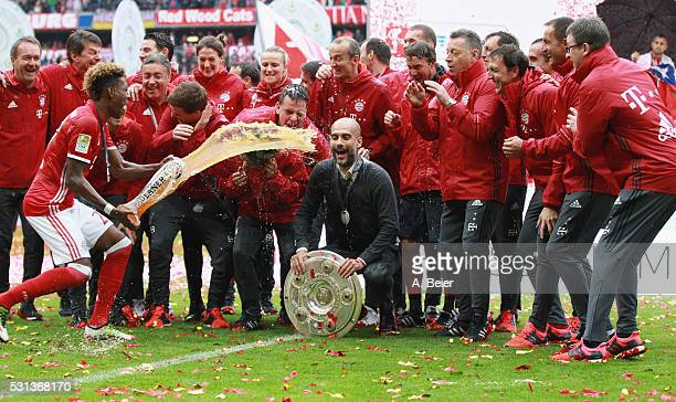Team coach Josep Guardiola of Bayern Muenchen receives a beer shower from David Alaba during the German Championship celebration after the Bundesliga...