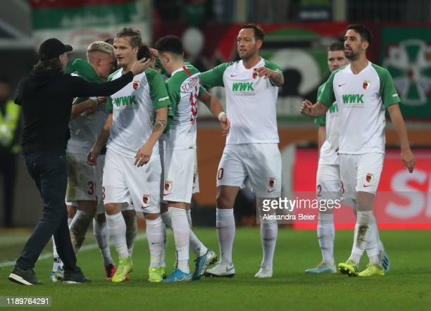 Team coach Martin Schmidt of FC Augsburg celebrates Florian Niederlechner's goal with players during the Bundesliga match between FC Augsburg and...