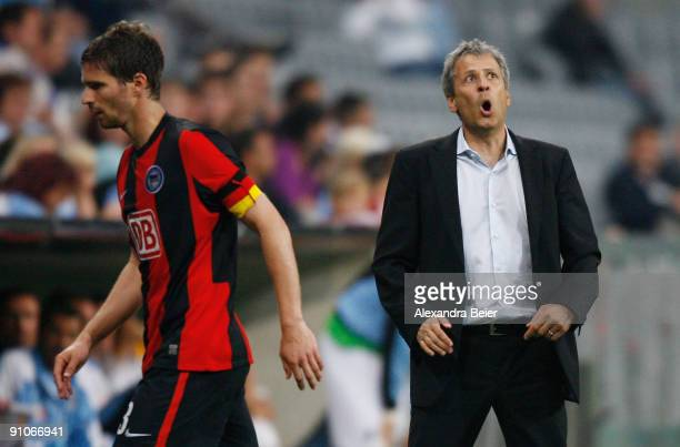 Team coach of Berlin Lucien Favre reacts as team captain Arne Friedrich passes by during the DFB Cup second round match between TSV 1860 Muenchen and...