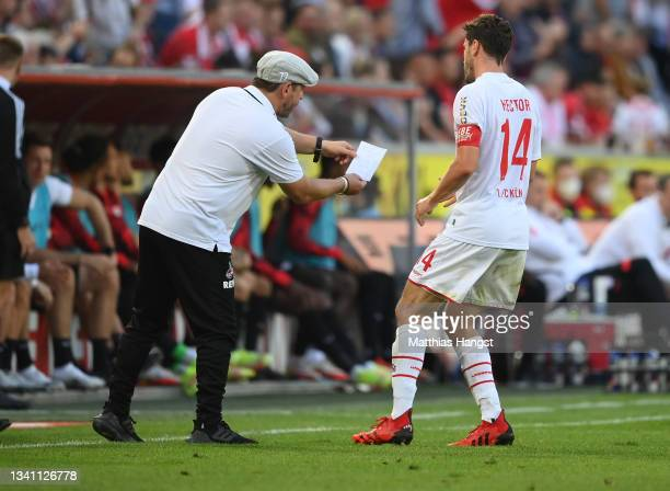 Team coach Steffen Baumgart of 1. FC Koeln shows a pice of paper to his player Jonas Hector during of the Bundesliga match between 1. FC Köln and RB...