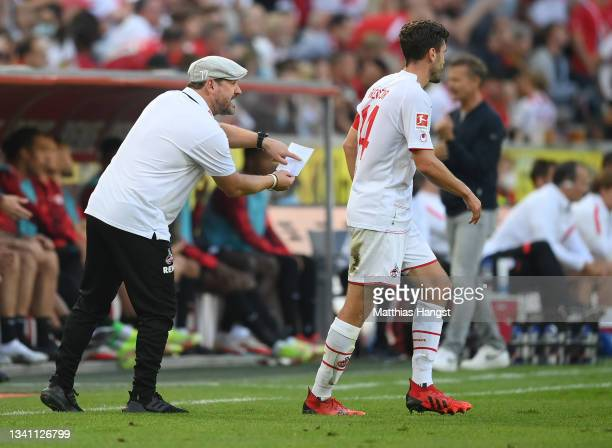 Team coach Steffen Baumgart of 1. FC Koeln shows a piece of paper to his player Jonas Hector during of the Bundesliga match between 1. FC Köln and RB...