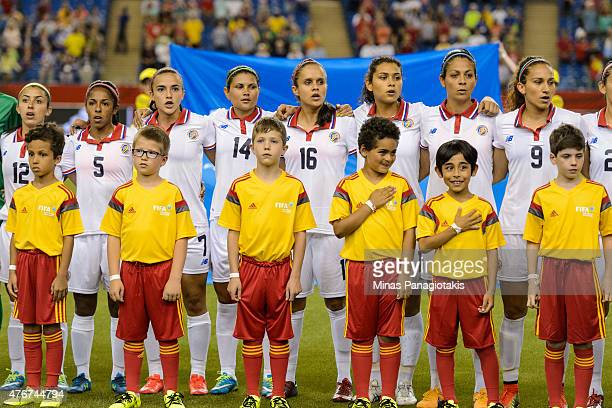 Team Costa Rica line up with the young player field escorts during the singing of the national anthem prior to the 2015 FIFA Women's World Cup Group...
