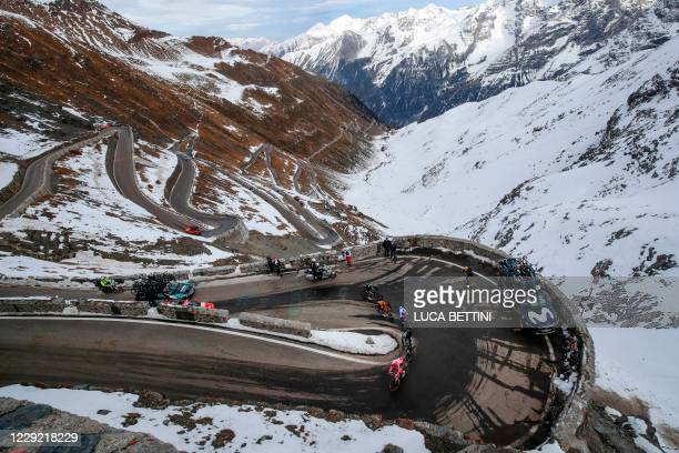 Team Deceuninck Portugal's rider Joao Almeida , wearing the overall Pink Jersey, leads the pack as they ride uphill at the Passo dello Stelvio during...