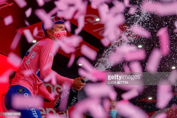 Team Deceuninck rider Portugal's Joao Almeida, wearing the overall leader's pink jersey, celebrates on the podium after the 4th stage of the Giro...