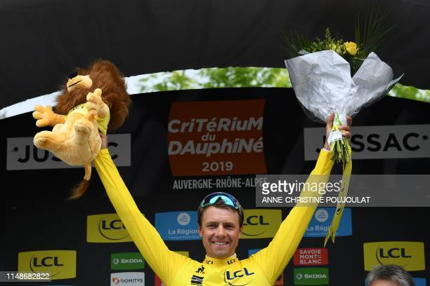 Team Dimension Data rider Norway's Edvald Boasson Hagen wearing the overall leader's yellow jersey celebrates on the podium after winning the first...