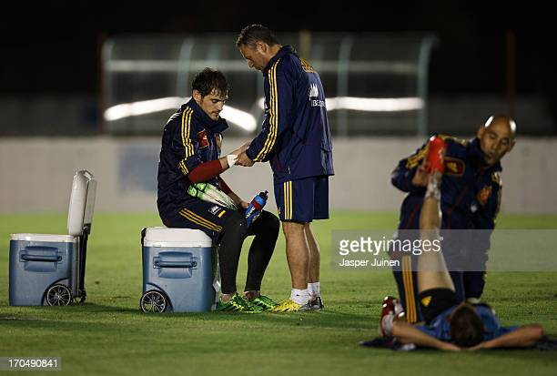 Team doctor Juan Garcia Cota removes tape around the hand of goalkeeper Iker Casillas of Spain at the end of a training session ahead of their FIFA...