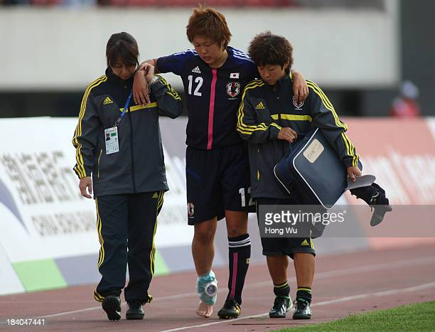 Team doctors hold Akane Saito of Japan after she injured during the 6th East Asian Games Women's Football match between Japan and North Korea at...