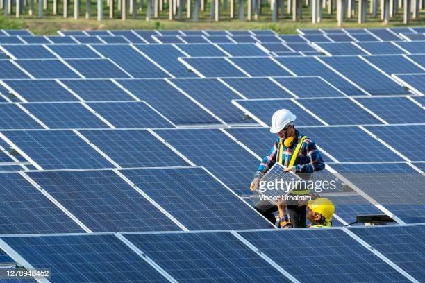 team electrician installing solar panels working on alternative energy sources clean. - steuerpult stock-fotos und bilder