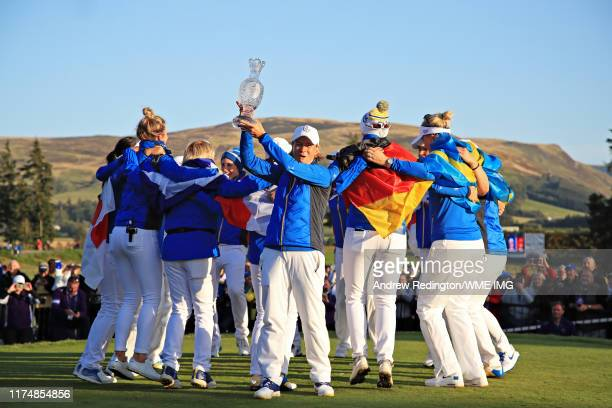 Team Europe captain Catriona Matthew holds the Solheim Cup as Team Europe celebrate winning the tournament behind during the final day singles...