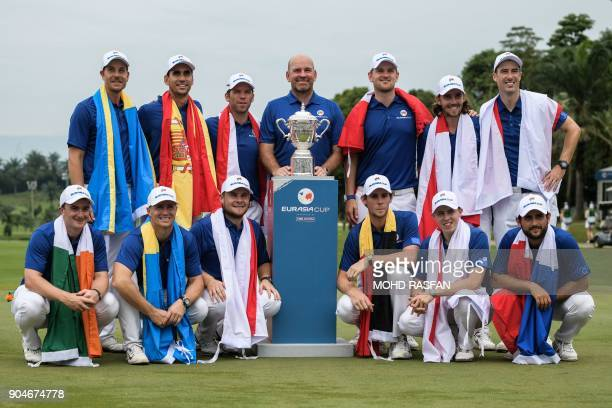 Team Europe's players pose for photographs with the trophy after winning the Eurasia Cup golf tournament at the Glenmarie Golf and Country club in...