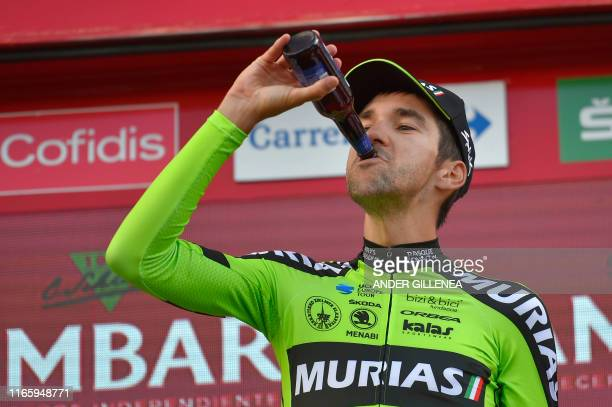 Team Euskadi Basque Country Murias rider Spain's Mikel Iturria drinks beer as he celebrates on the podium after winning the eleventh stage of the...