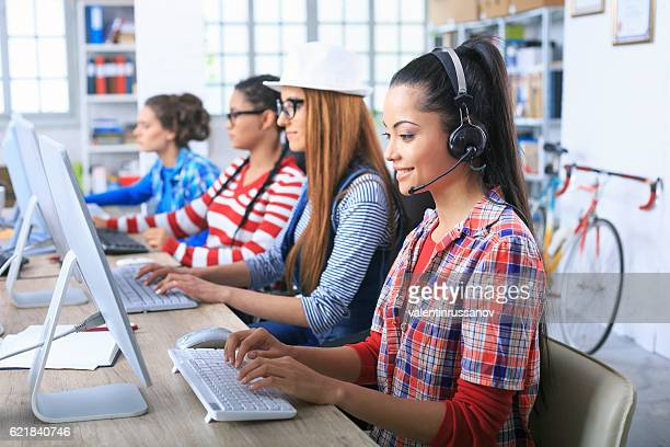 Team female call centre coworkers using computers in office