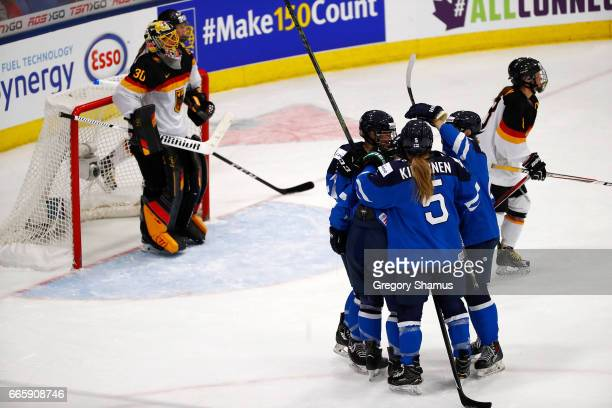 Team Finland celebrate a first period goal next to Jennifer Harss of Germany in the bronze medal game at the 2017 IIHF Woman's World Championships at...