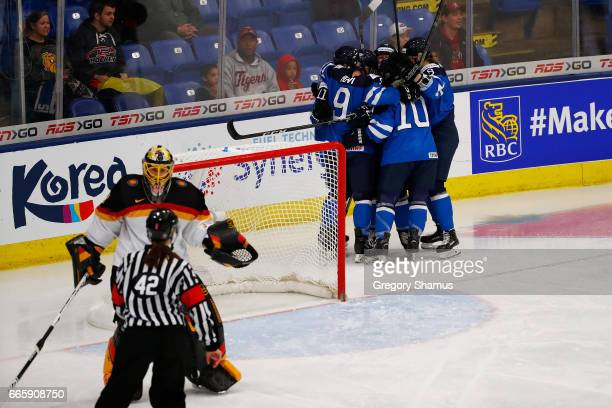Team Finland celebrates a first period goal while Jennifer Harss of Germany arguers with the referee about the goal in the bronze medal game at the...