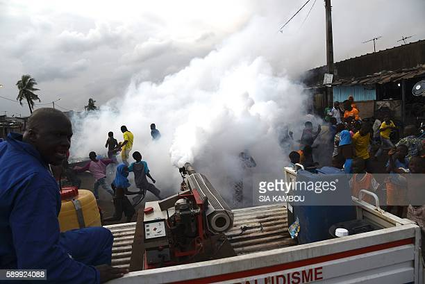 A team from the National Institute of Public Health sprays anti mosquito product through the Koumassi district as people stand in the street of...