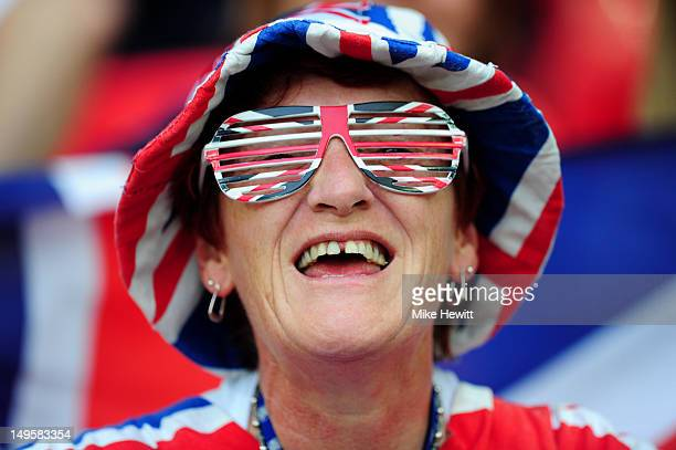Team GB fan wearing a Union Jack hat and glasses smiles before the Women's Football first round Group E Match between Great Britain and Brazil on Day...