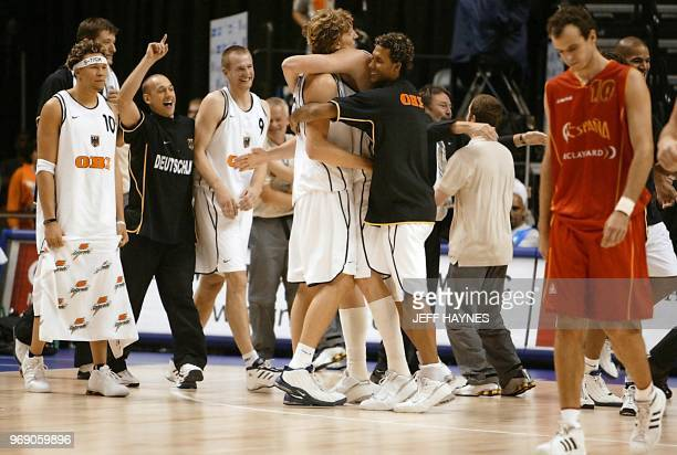 Team Germany celebrates as Carlos Jimenez of Spain walks off the court 05 September, 2002 after their quarter finals game of the 2002 Men's FIBA...