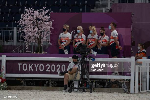 Team Great Britain members wearing face masks watch as teammate Sophie Wells competes with their horse Don Cara .M in the Dressage Team Test to Music...