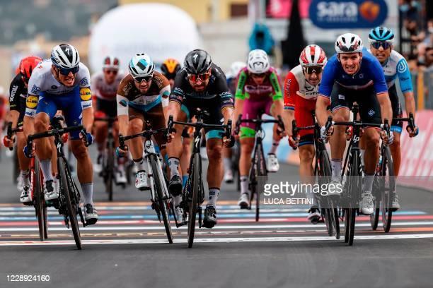 Team Groupama-FDJ rider France's Arnaud Demare crosses the finish line to win, ahead of Team Bora rider Slovakia's Peter Sagan and Team Deceuninck...