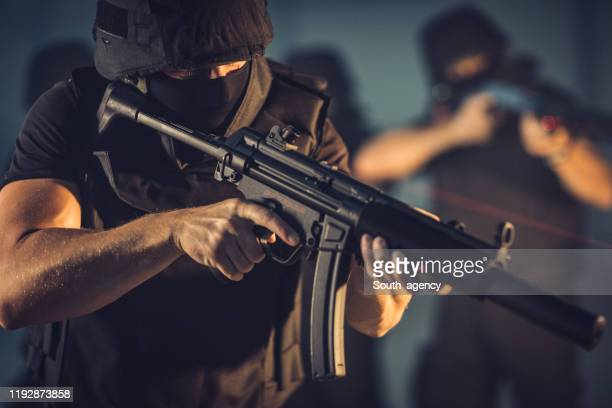 swat team guy aiming with machine gun - south_agency stock pictures, royalty-free photos & images