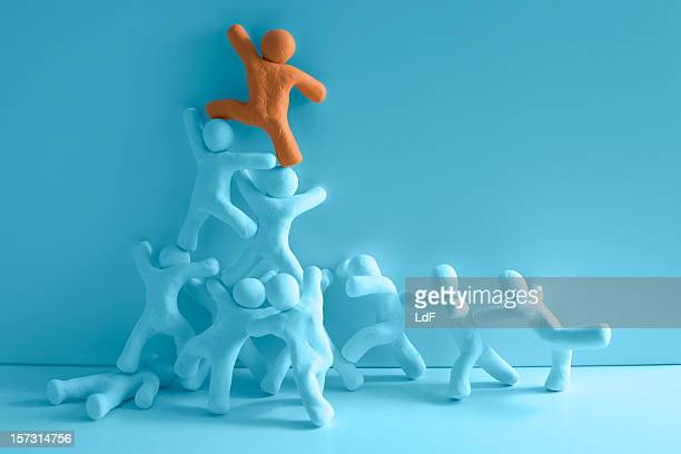team helping the leader - clay stock pictures, royalty-free photos & images