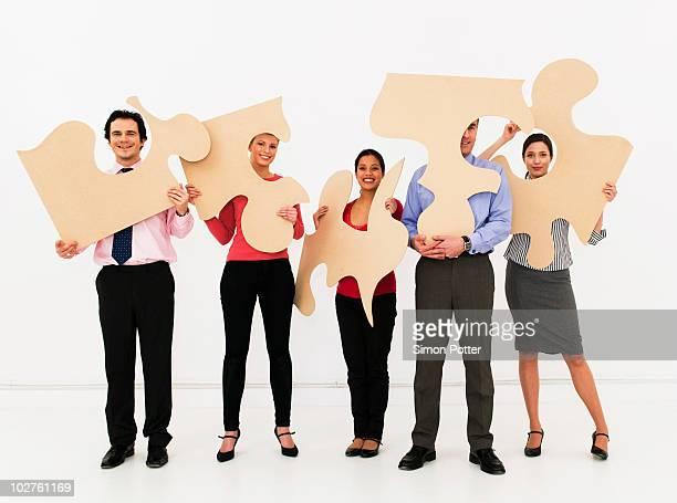 Team hold jigsaw pieces