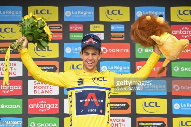 Team Ineos' Richie Porte of Australia celebrates his overall leader's yellow jersey on the podium at the end of the eighth stage, on the final day of...