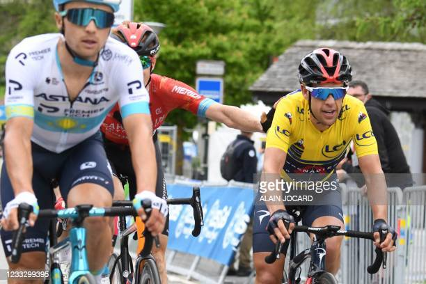 Team Ineos' Richie Porte of Australia wearing the overall leader's yellow jersey celebrates as he crosses the finish line of the eighth stage after...
