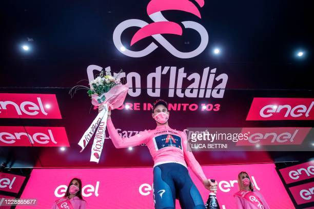 Team Ineos rider Italy's Filippo Ganna, wearing the overall leader's pink jersey, celebrates on the podium after winning the first stage of the Giro...