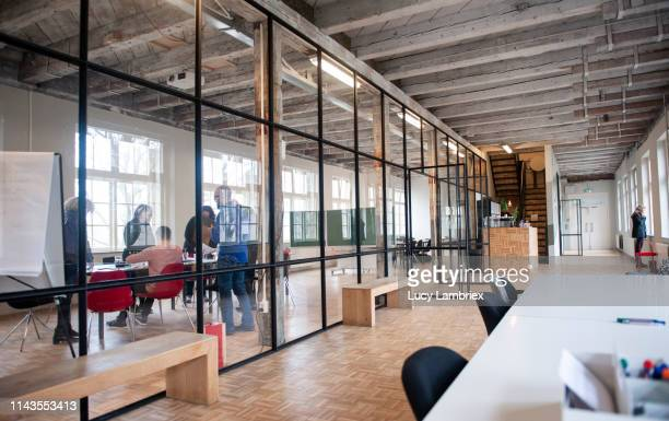 a team is working behind glass in a large modern office space - kontor bildbanksfoton och bilder