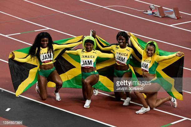 Team Jamaica celebrate gold after the women's 4x100m relay final during the Tokyo 2020 Olympic Games at the Olympic Stadium in Tokyo on August 6,...