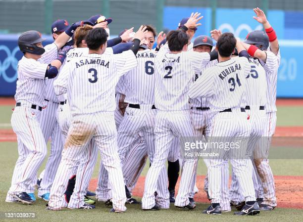 Team Japan celebrate with teammate Hayato Sakamoto after his walk-off in the ninth inning to win 4-3 against Team Dominican Republic during the...